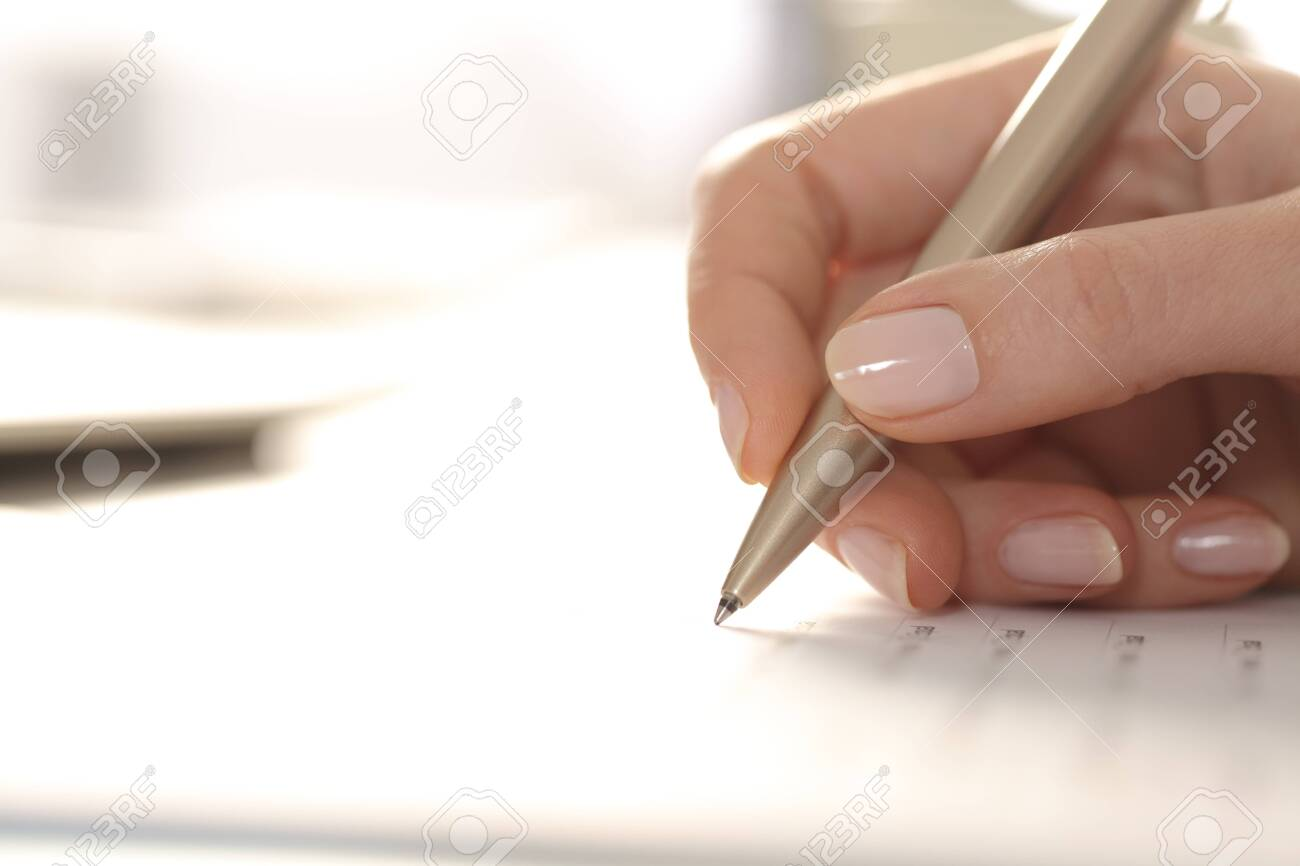 Close up of woman hand filling out form with pen on a desk - 144517200