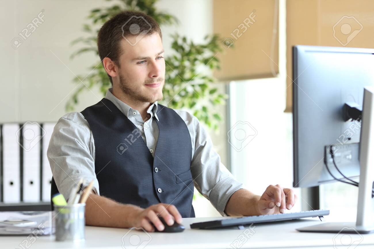 Concentrated executive man using computer sitting on a desk at the office - 145050175
