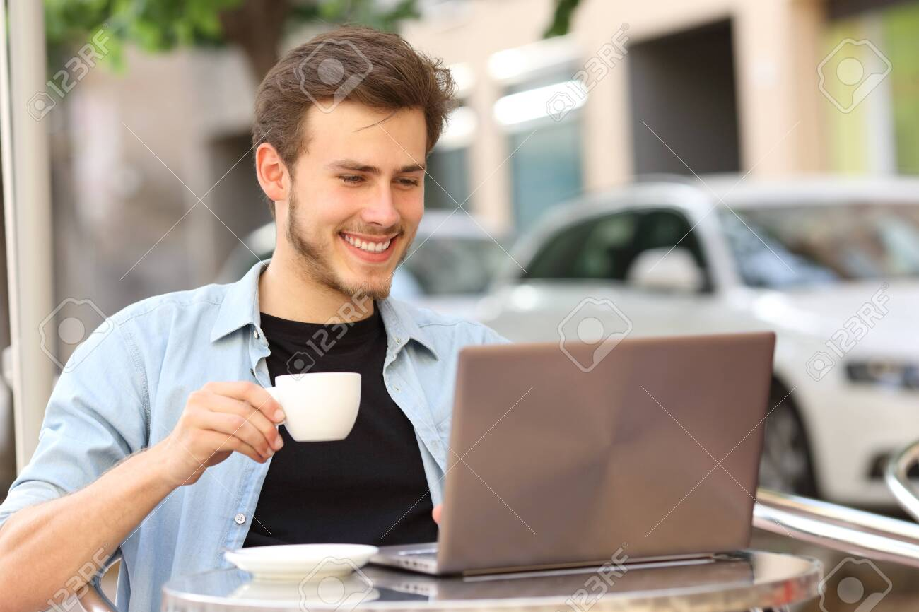Happy man reading on laptop holding cup sitting on a coffee shop terrace - 148020044