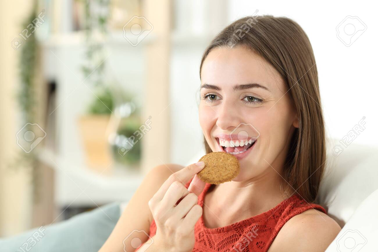Happy woman is eating cereal cookie sitting on a couch in the living room at home - 155665926