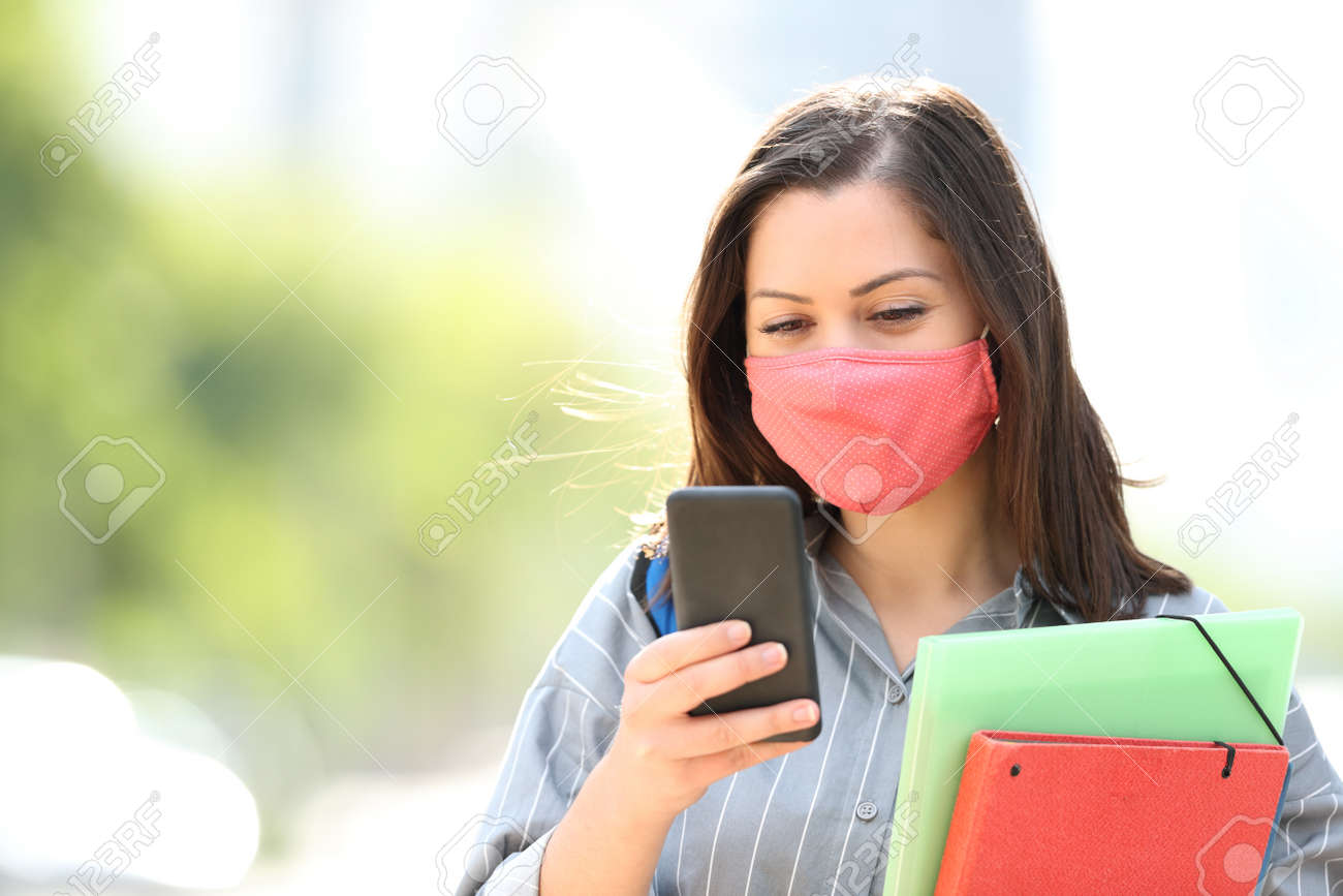 Student with mask avoiding coronavirus or pollution using smart phone walking in the street - 159063948