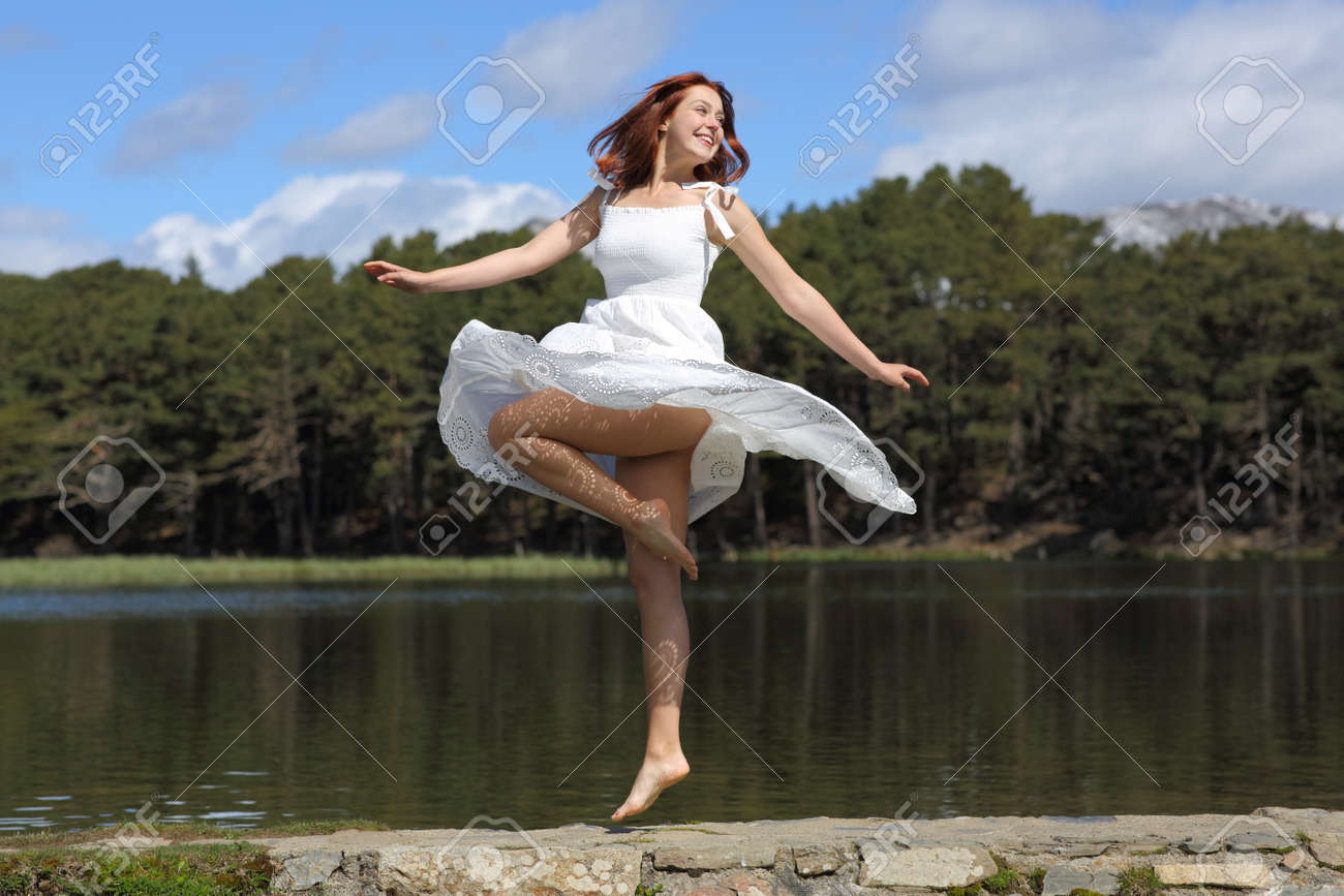 Happy woman in white dress twirling showing waxed legs in a lake - 170946558