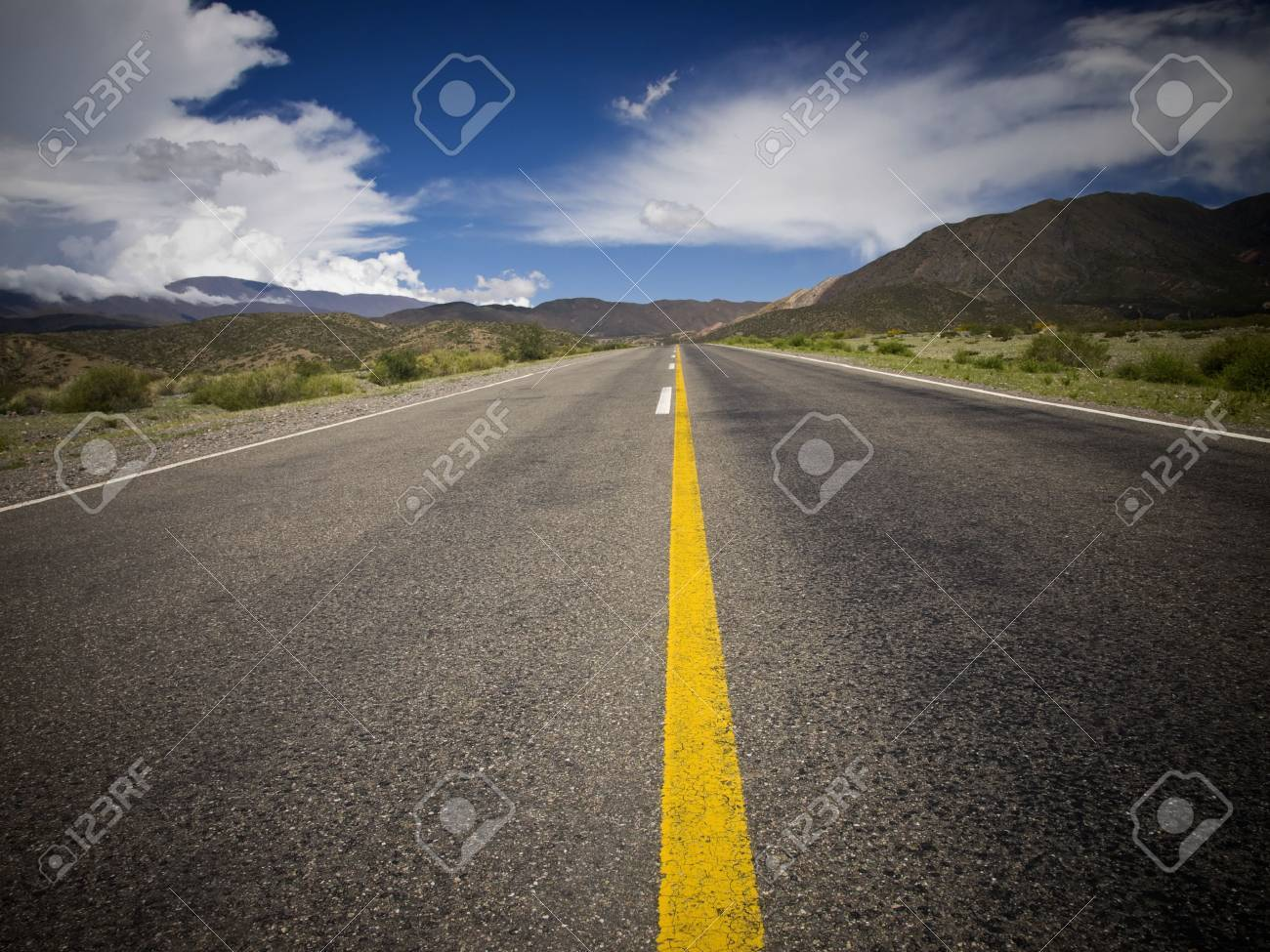 A desert road by the mountains surrounded by colorful nature. Stock Photo - 4802518