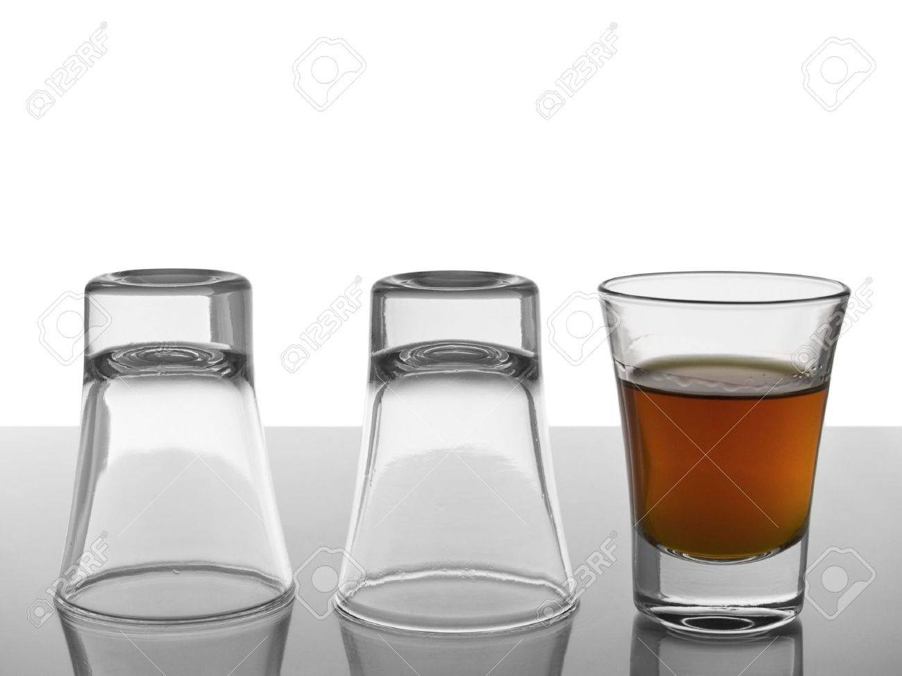 Two empty shots upside down and a third one full of liquor. Stock Photo - 4802504