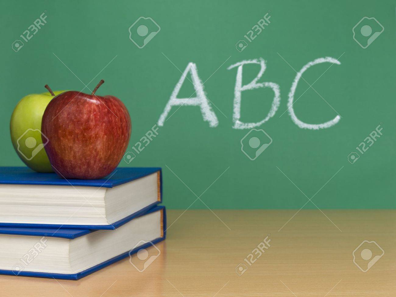 ABC written on a chalkboard. Two apples over books on the foreground. Stock Photo - 5322453