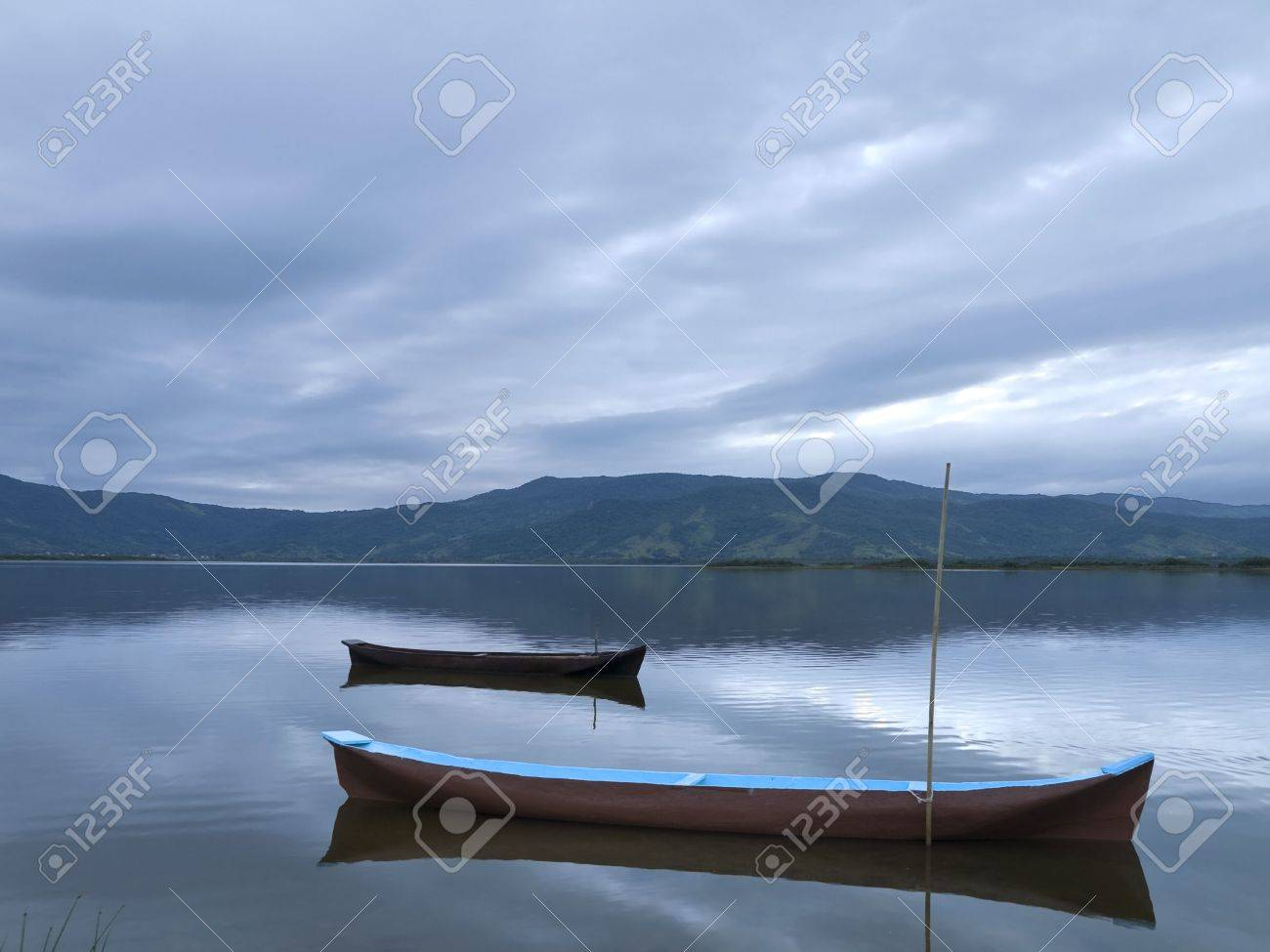 Two canoes tied on a quiet lake under a cloudy sky. Stock Photo - 5828728