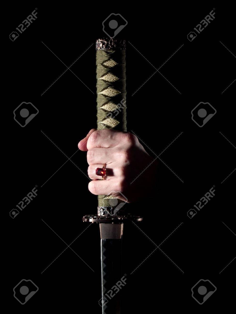 Japanese katana sword in man's hand in darkness - 4295804