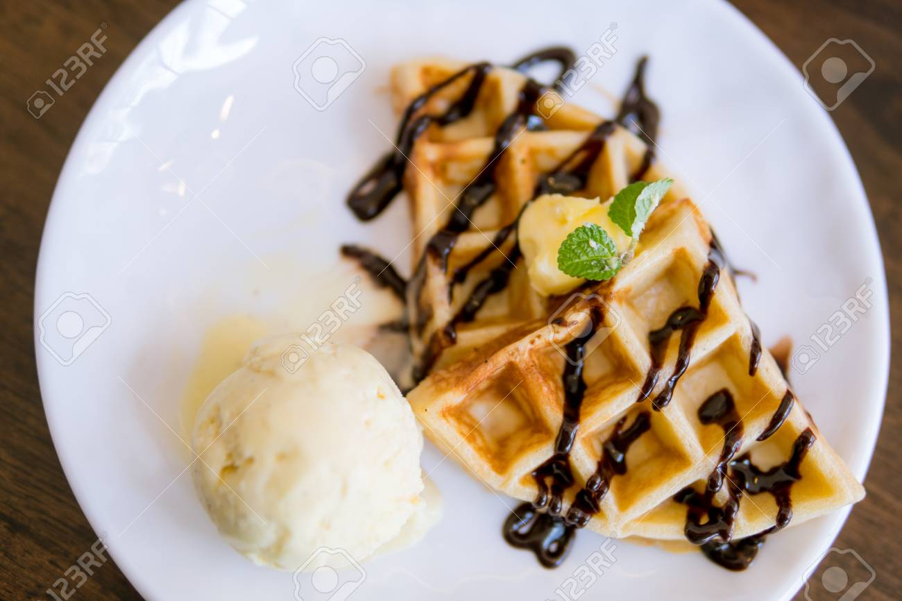 Waffles with ice cream with chocolate and mint leaf - 97483063