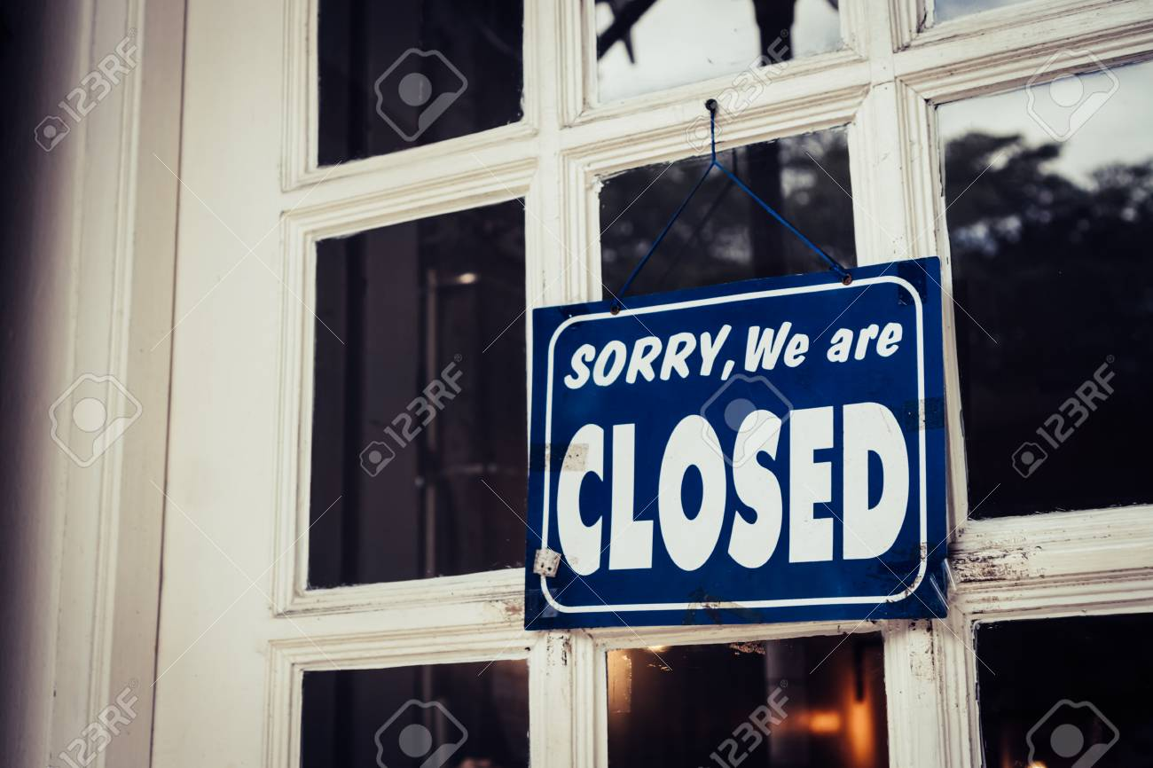 A Sign board of sorry we are closed hang on door of business shop with nature green background - 113372638