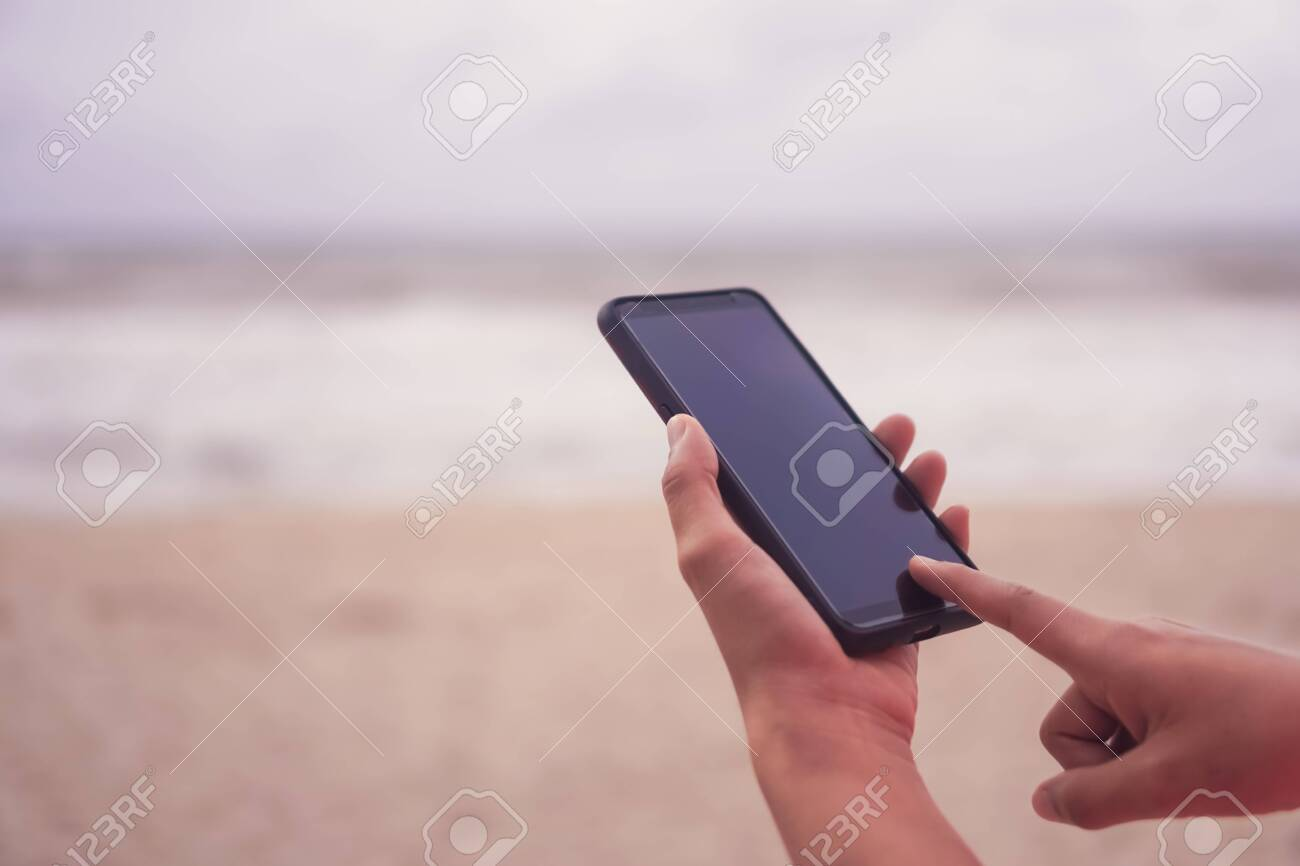 Woman hand use smartphone to do work business, social network, communication in public cafe work space area. - 146184596
