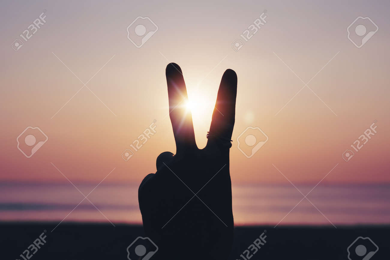 Peace out or fighting metaphor two fingers hand sign in front of a sunset. Happy people enjoying nature. - 173248947