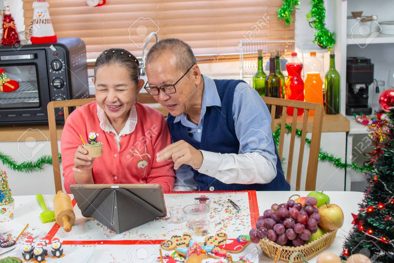 Senior An Asian grandfather and grandmother wearing aprons learning to make cupcake online with a tablet having fun in a kitchen. - 157162138