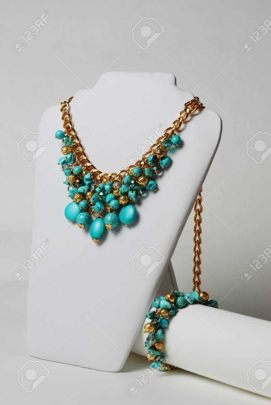 orden buscar original mejor selección Collar con turquesa, piedras preciosas naturales y la cadena de oro sobre  un maniquí en frente de fondo blanco