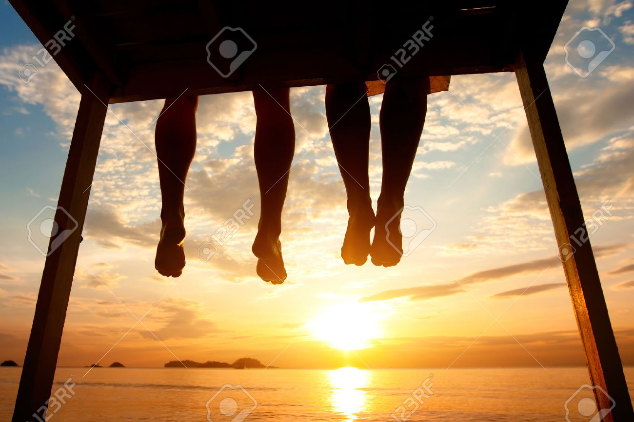 silhouette of feet of couple sitting on the pier at sunset beach, low angle view - 53068853