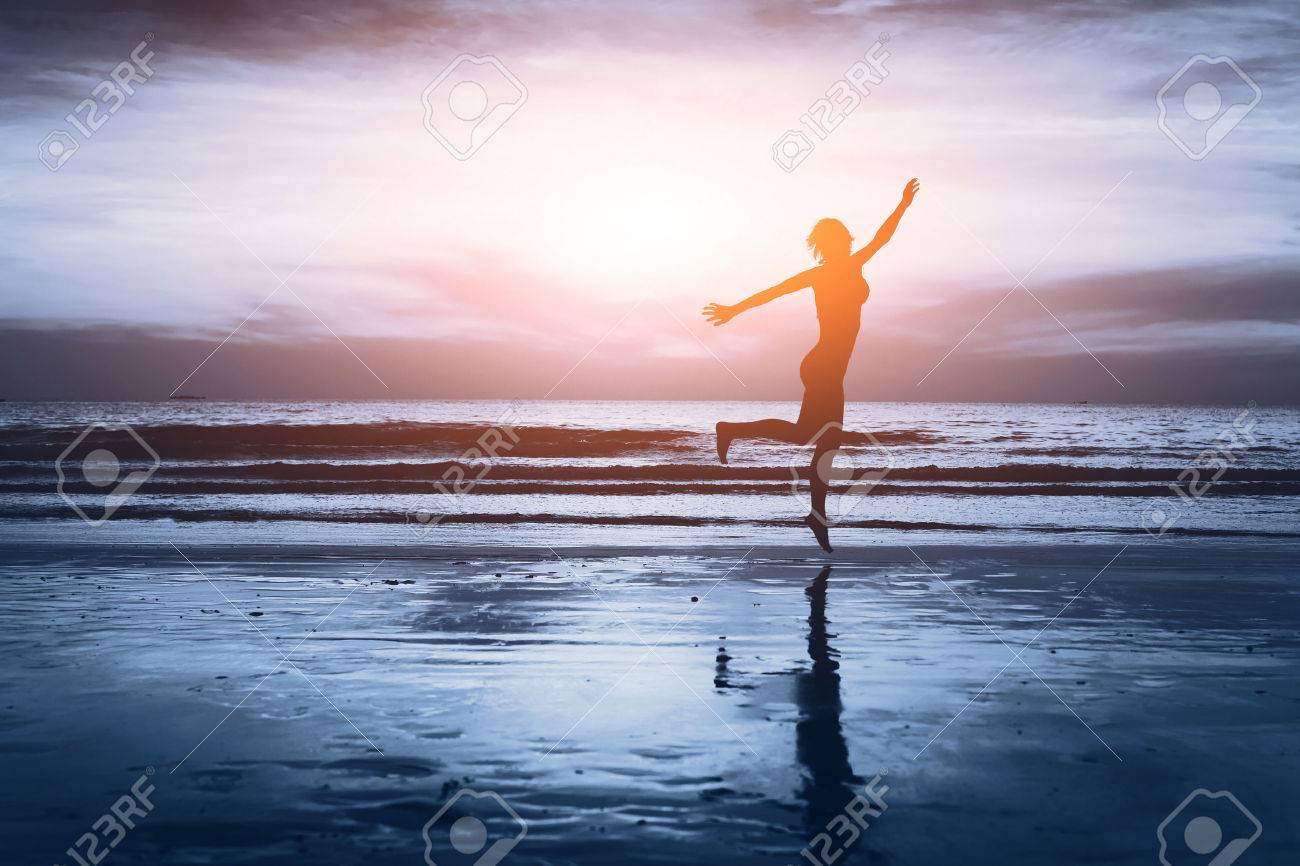 healthy life, silhouette of carefree woman on the beach Stock Photo - 53069183