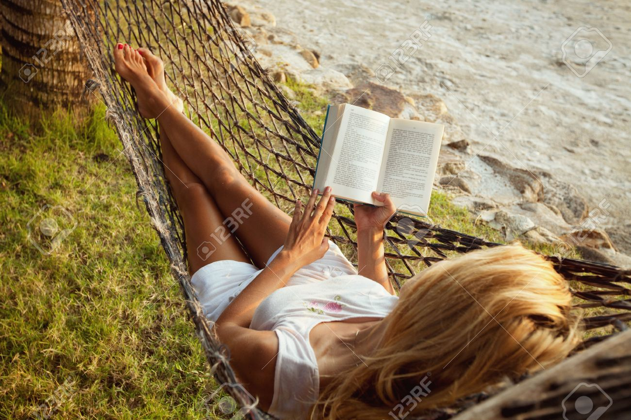 Woman lying in a hammock on the beach and enjoying a book reading - 53072400
