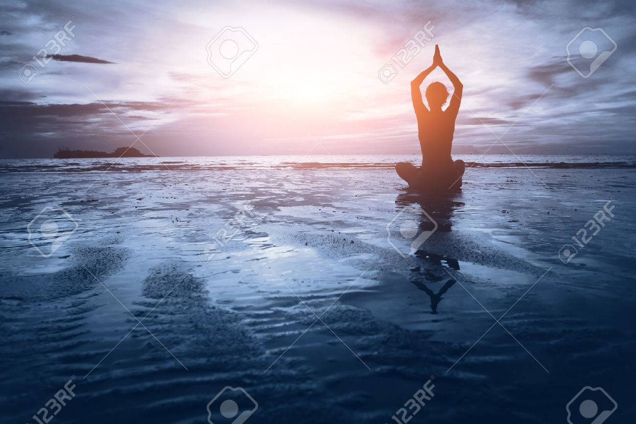 well being concept, beautiful sunset on the beach, woman practicing yoga - 53075198