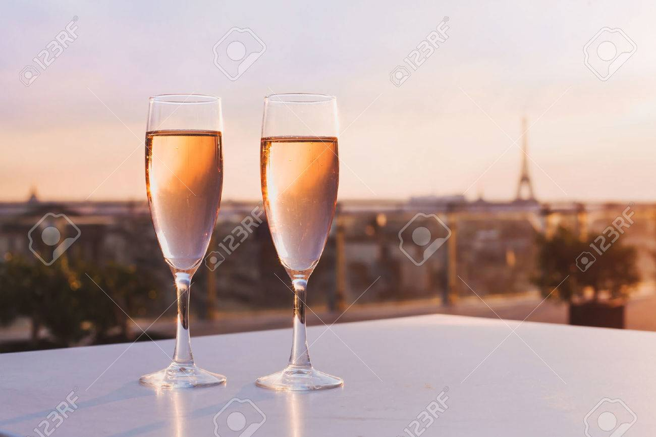 two glasses of champagne at rooftop restaurant with view of Eiffel Tower and Paris skyline, luxury romantic dinner for couple - 68680397