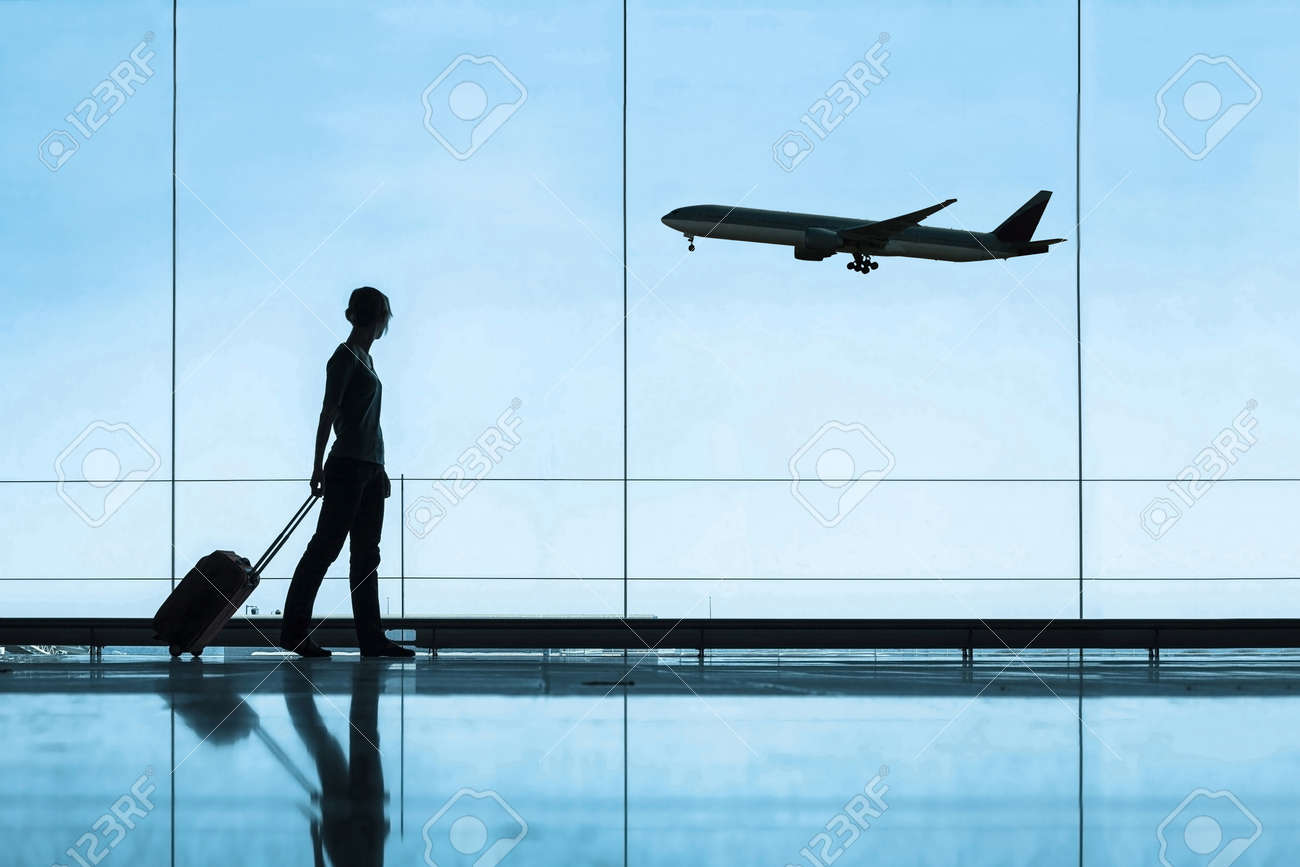 silhouette of woman in airport traveling with luggage suitcase, travel and tourism concept, airplane tickets - 145004865