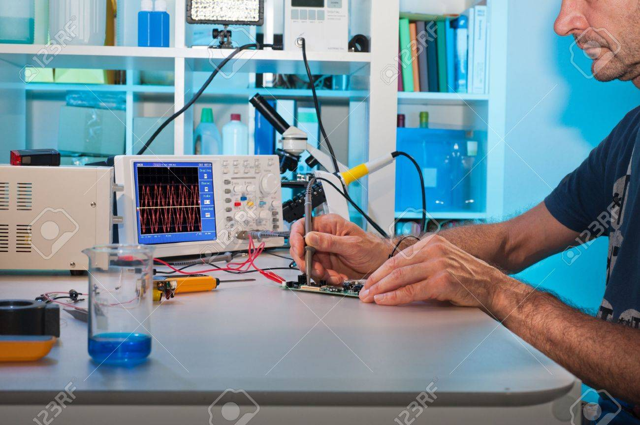 An engeneer tests electronic components with oscilloscope in the service centre Stock Photo - 14642009