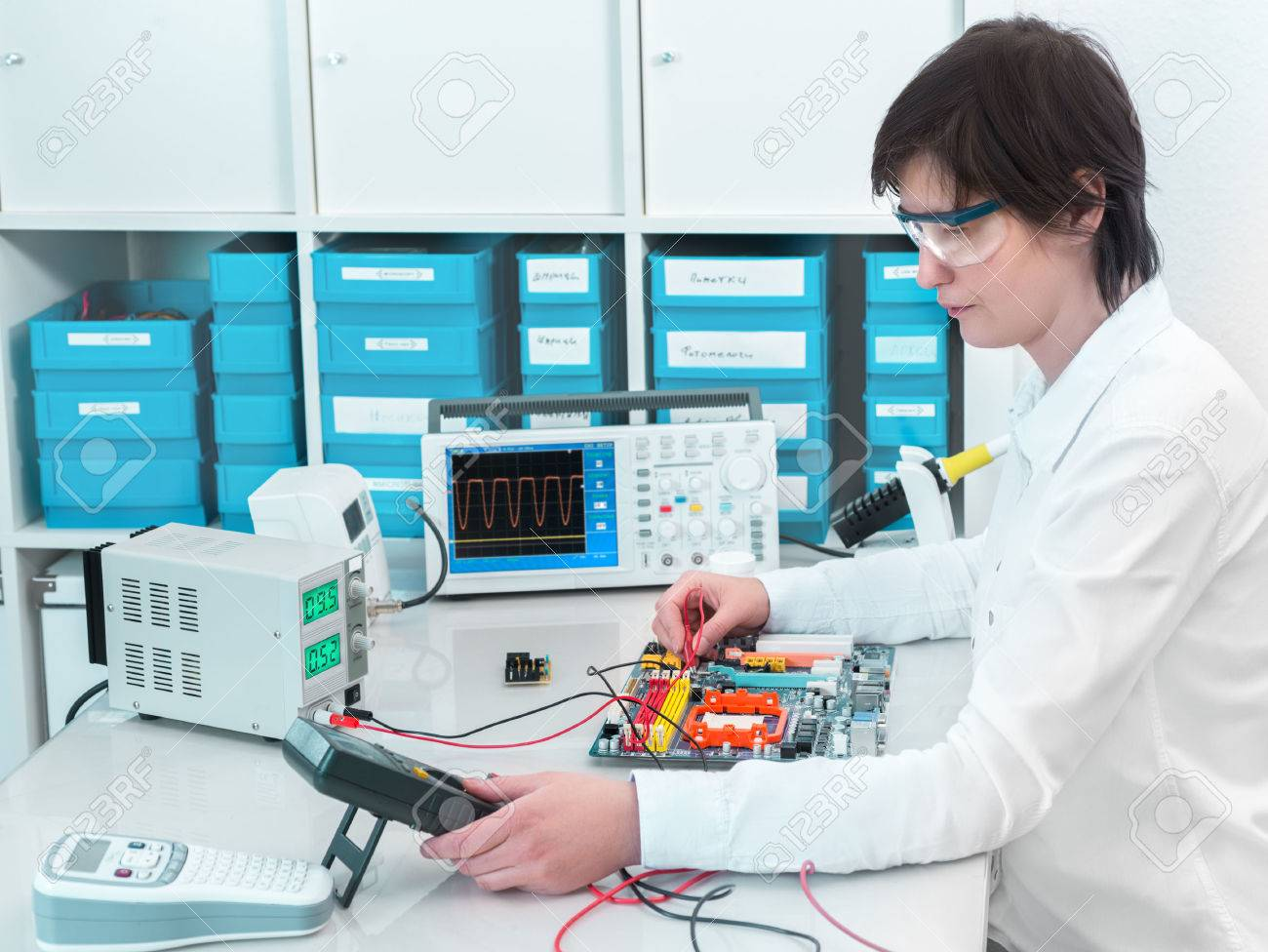 Tech tests electronic equipment in service center - 31077159