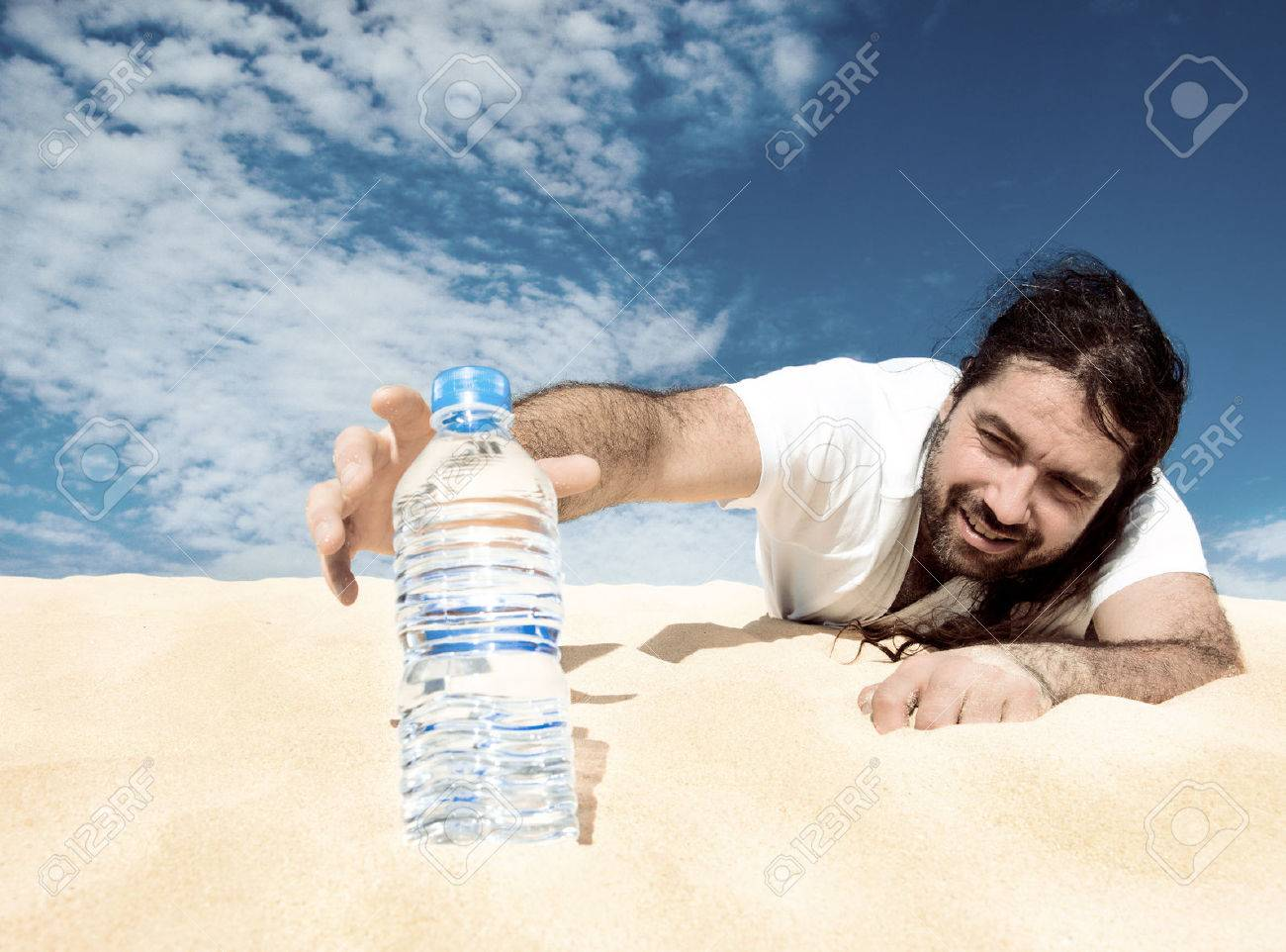 Thirsty man in the desert reaches for a bottle of water, toned image - 32842327