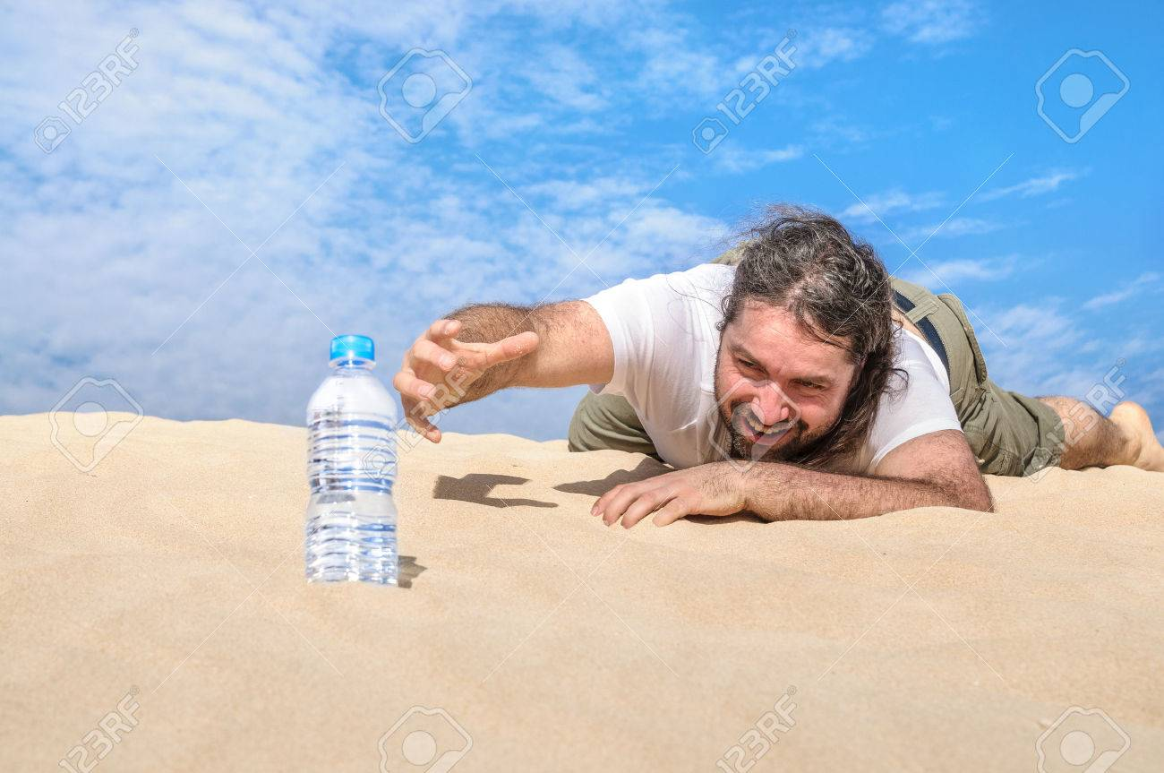 thirsty man in the desert reaches for a bottle of pure water stock