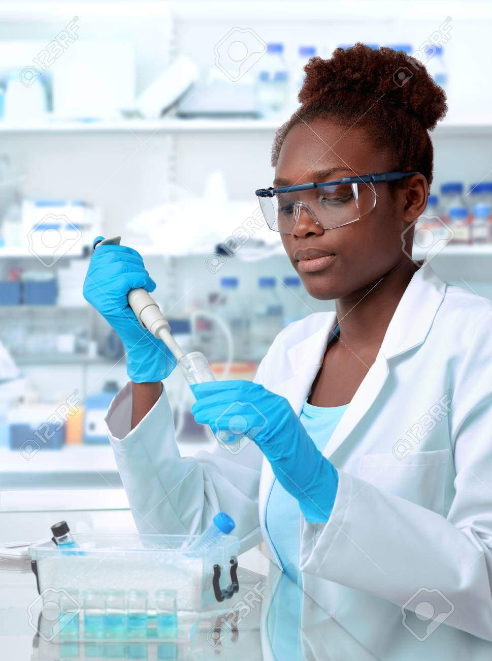 African-american scientist or graduate student in lab coat and protective wear works in modernl laboratory - 92485347