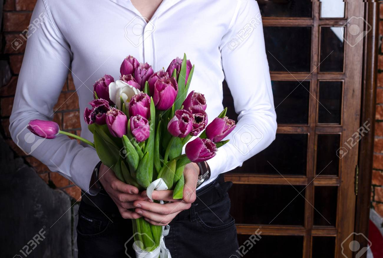 A Bright Bouquet In The Hands Of A Young Man In A White Shirt ...