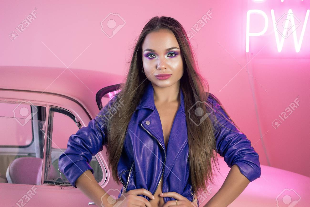69c994bf6 Sexy Girl In Blue Leather Jacket And Black Shorts Against A Pink ...