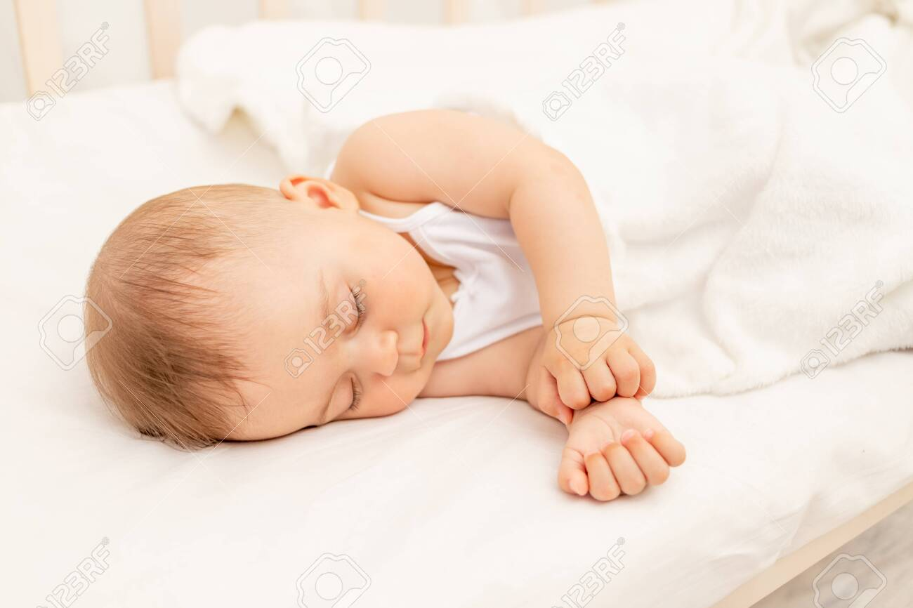Small baby girl 6 months old sleeping in a white bed, healthy baby sleep - 152333537
