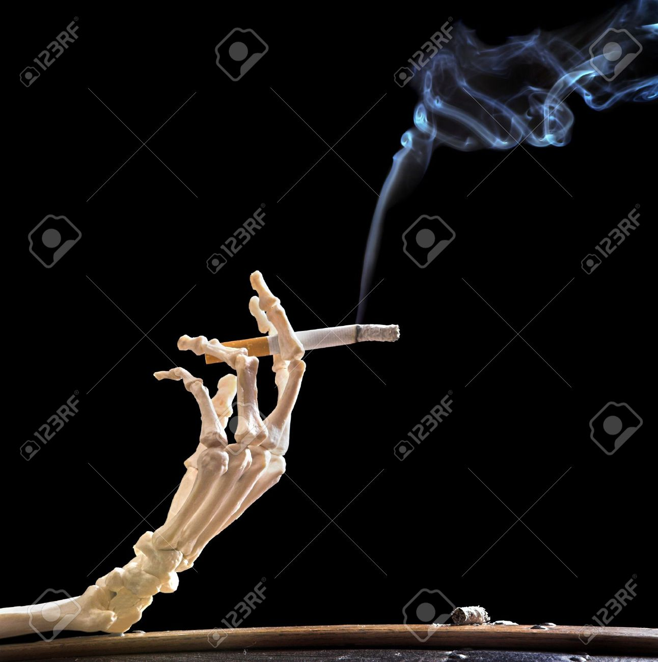 Hand of death holding a smoking cigarette Stock Photo - 3701360