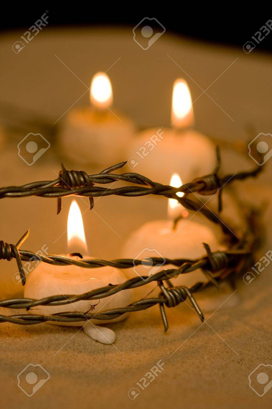 Burning candles behind barbed wire, symbol of hope Stock Photo - 4037829