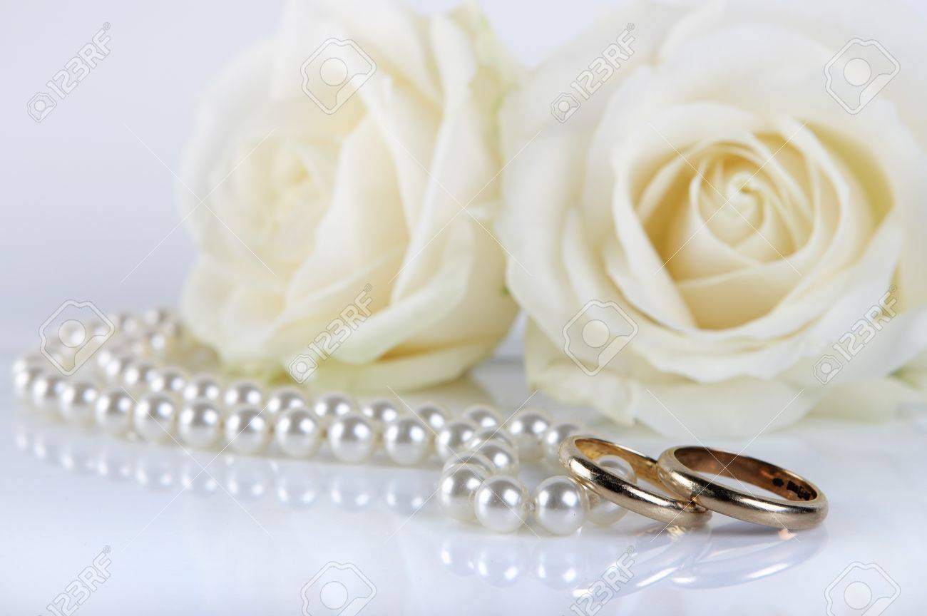 Couple Of Worn Wedding Rings And Pearls, With Two Fresh White Roses Stock  Photo