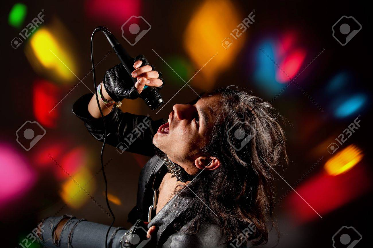 Young handsome rock singer against a dark background with spot lights Stock Photo - 4404531