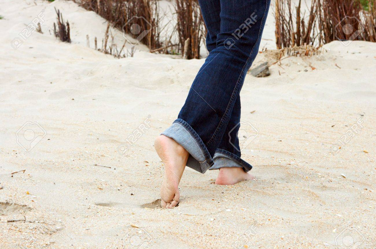 Feet of a young woman walking in the sand on the beach Stock Photo - 4869793