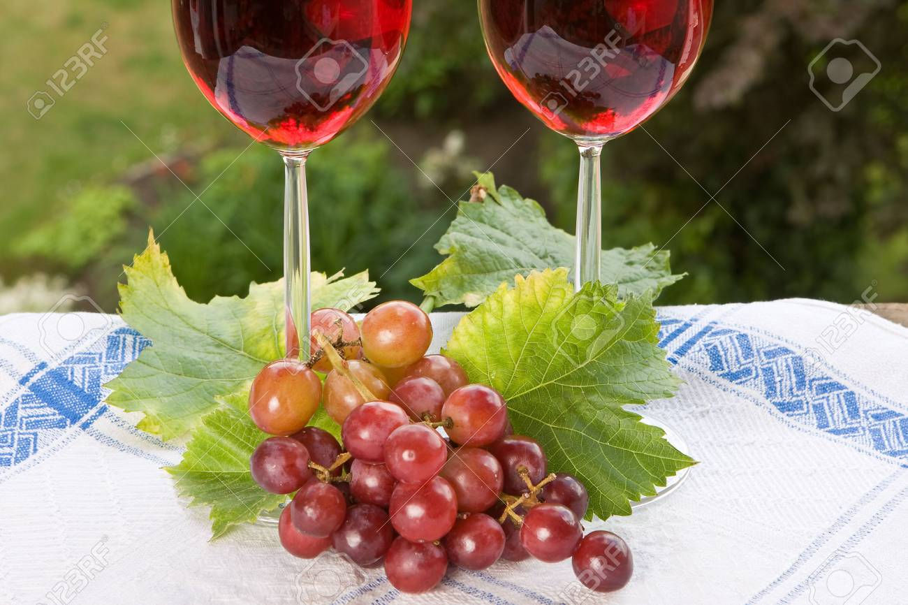 Two wine glasses filled with red wine in a summer setting Stock Photo - 4967724