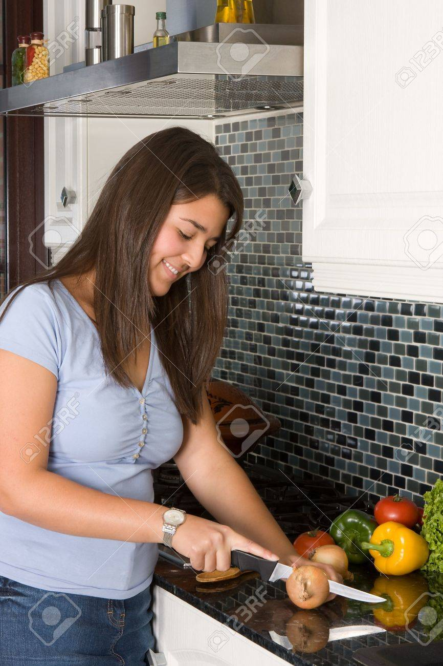 Young woman smiling while cutting onions in the kitchen Stock Photo - 5147726