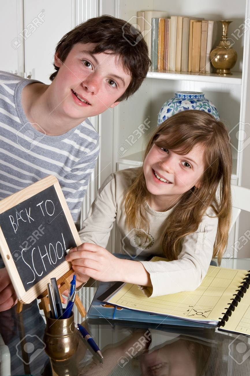 Two teenagers writing Back to School on a small blackboard Stock Photo - 5265789