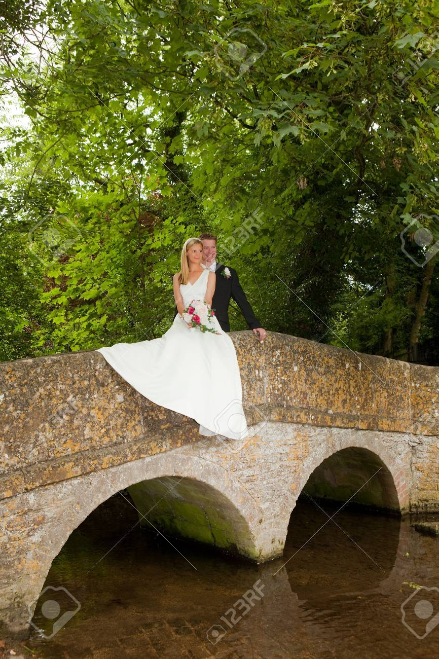 Loving newly wed couple posing on a medieval grunge packhorse bridge Stock Photo - 5343572