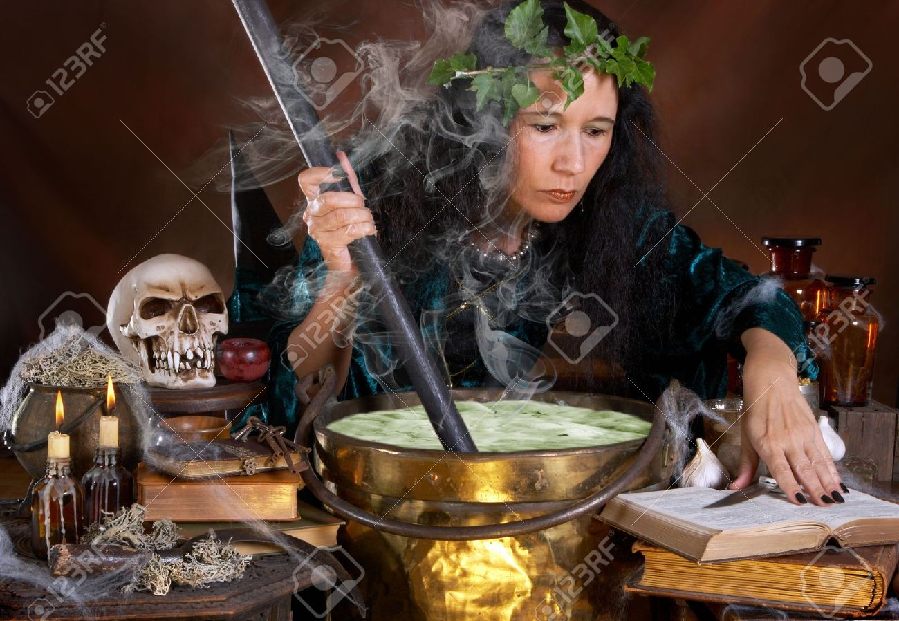 Halloween witch stirring in green poison soup in her cauldron Stock Photo - 5495802