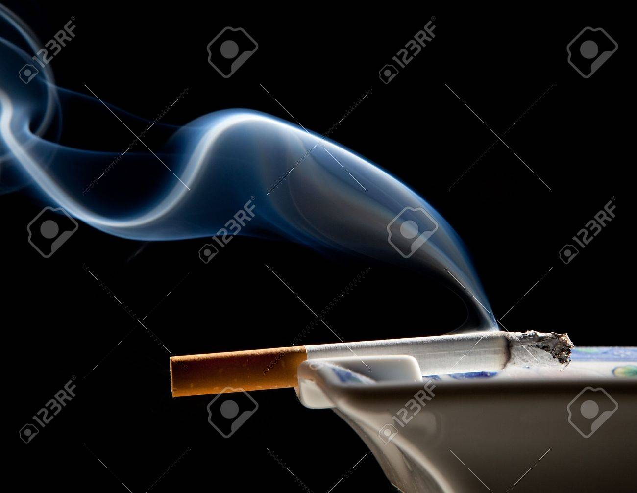 Cigarette on ashtray with a beautiful wisp of smoke Stock Photo - 5565927