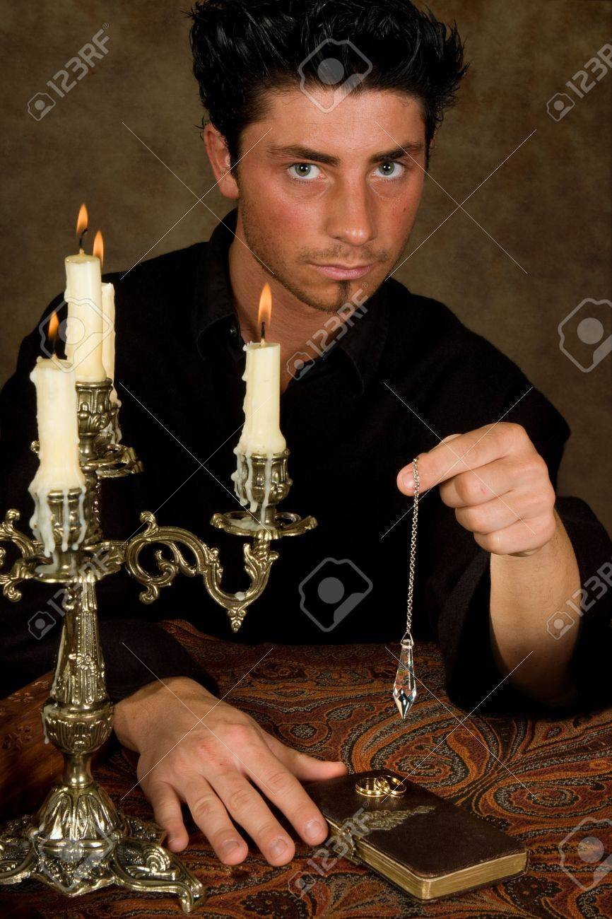 Astrologist holding a pendulum above wedding rings, to see if the baby will be a boy or a girl Stock Photo - 5674502