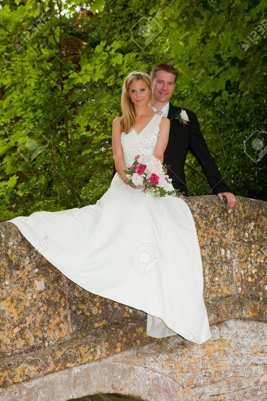 Loving newly wed couple posing on a medieval grunge packhorse bridge Stock Photo - 6166259