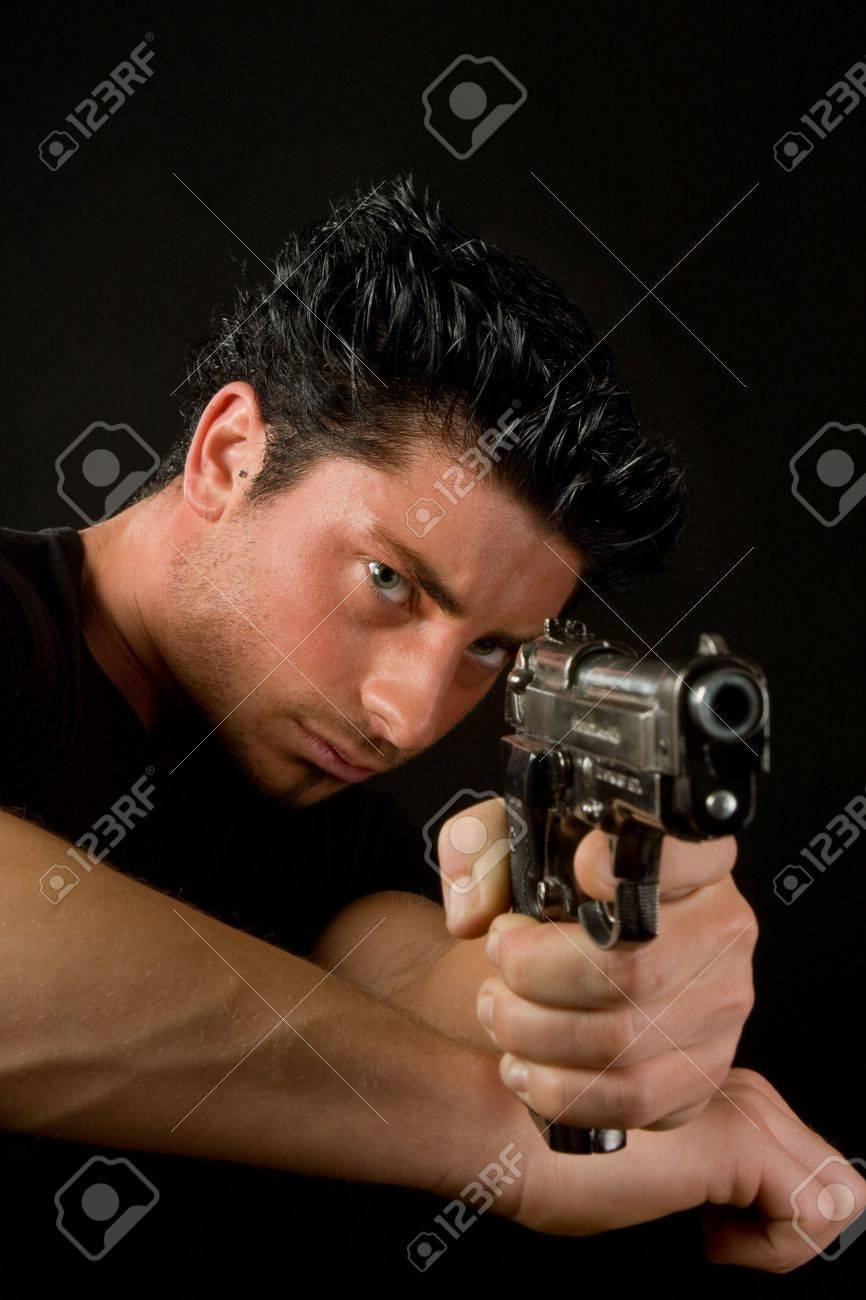 Young man aiming and firing a deadly weapon Stock Photo - 6431311