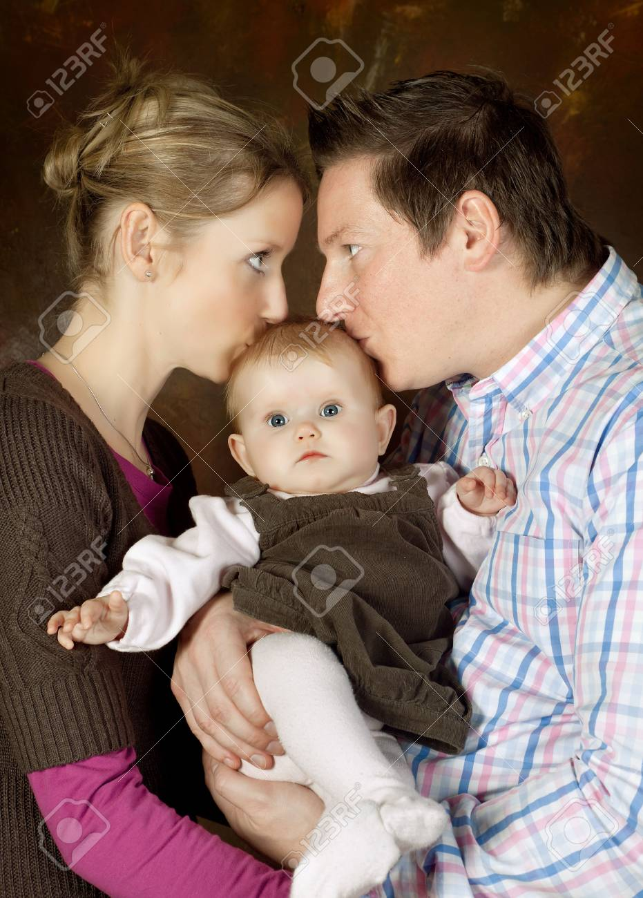 Happy mother and father kissing their 4 months old baby Stock Photo - 6681717