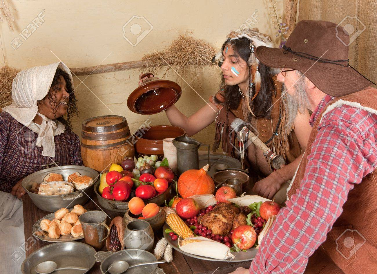 Reenactment scene of the first Thanksgiving Dinner in Plymouth in 1621 with a Pilgrim family and a Wampanoag Indian Stock Photo - 7686138