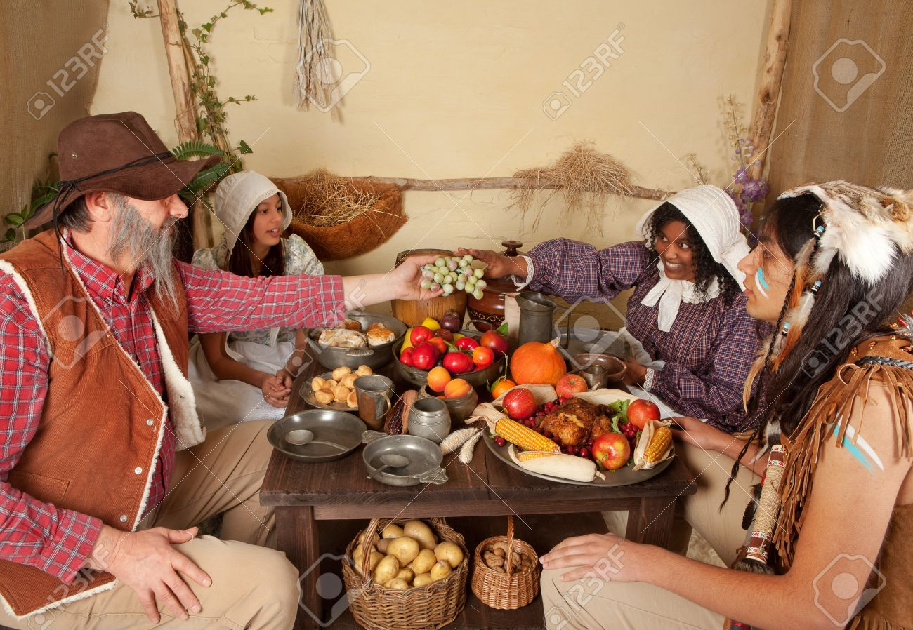 Reenactment scene of the first Thanksgiving Dinner in Plymouth in 1621 with a Pilgrim family and a Wampanoag Indian Stock Photo - 7686214