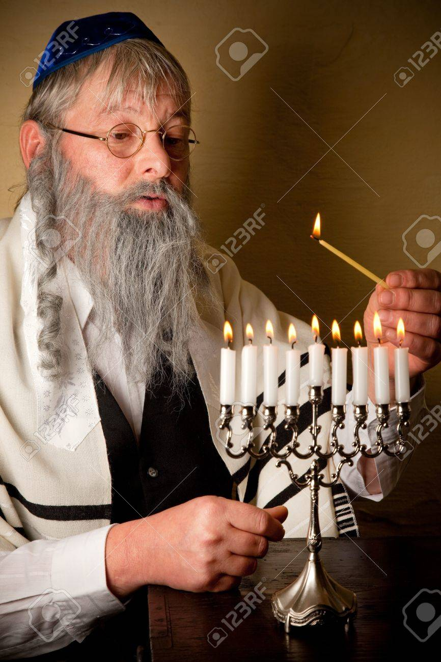 Old Jewish Man With Beard Lighting The Candles Of A Menorah Stock Photo    7795465