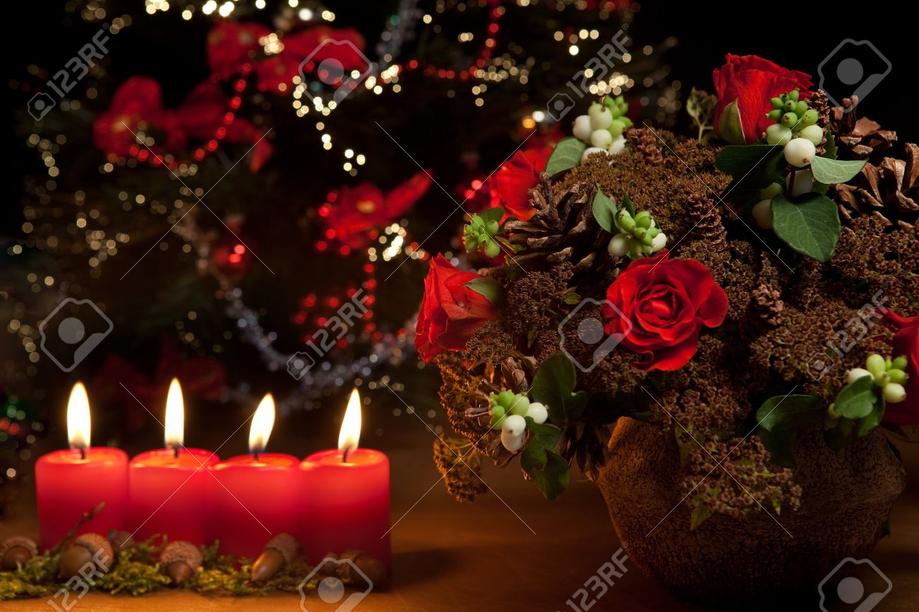 Christmas candles, flower arrangement and blurred christmas tree Stock Photo - 8301341